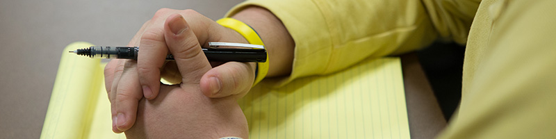 A student wearing a yellow fleece writing on a notepad with a yellow pencil