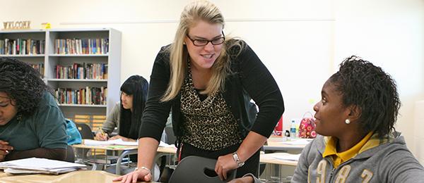 Woman teaching two high school students