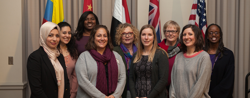 Global Sisterhood award recipients pose near flags of many nations