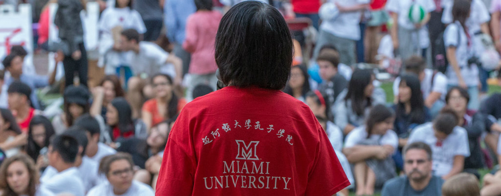A Confucius Institute staffer wearing a Chinese language Miami t-shirt addresses a crowd at the Uptown Parks
