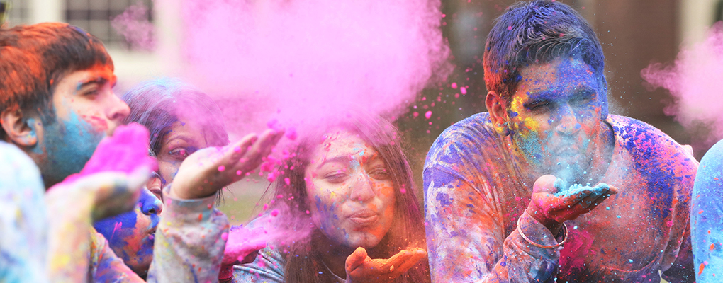 Students celebrate Holi as they puff clouds of color into the air