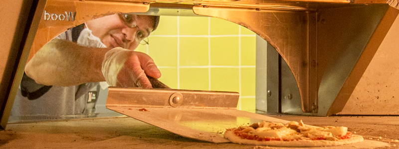 A member of dining staff places a freshly prepared pizza into a wood burning oven