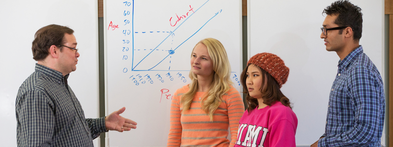 A faculty member explains a graph on a white board to three students