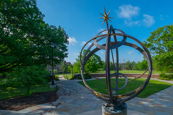 The sundial gleams under a bright blue sky