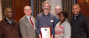 A group of faculty pose with an award plaque