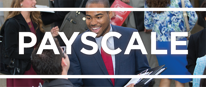 White text that says Payscale on top of a photo of two people talking at career fair
