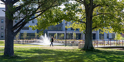 A student walks by Upper Pond and Hillcrest Residence Hall.