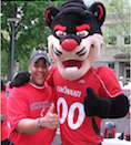 Michael Southern wearing a red Cincinnati t-shirt and hat standing the the University of Cincinnati Bearcat mascot