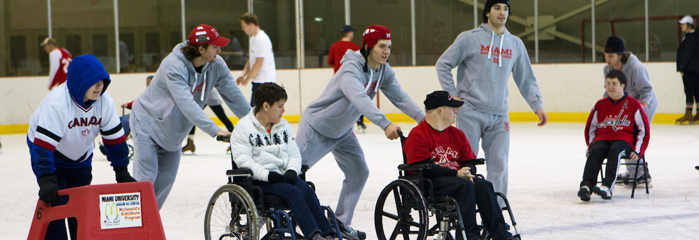 Members of Best Buddies being wheeled around ice rink by Miami hockey players