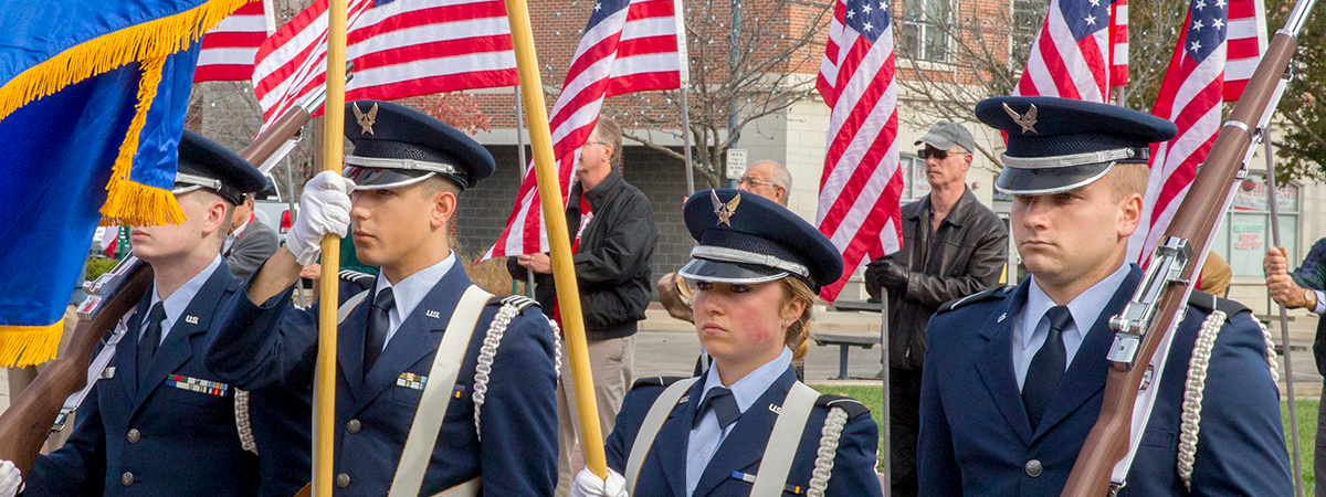 ROTC students standing at attention holding flags and guns