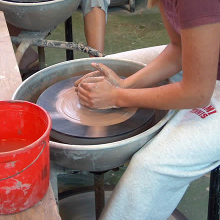 A woman works clay at a pottery wheel