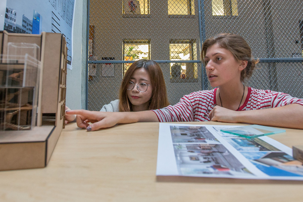 Two students review their work inside the cage gallery