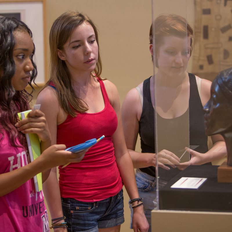 Three Miami students observe a dark stone bust