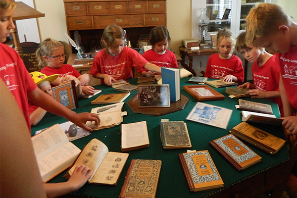 Children examine a selection of McGuffey Readers arrayed on McGuffey's famous green octagonal table