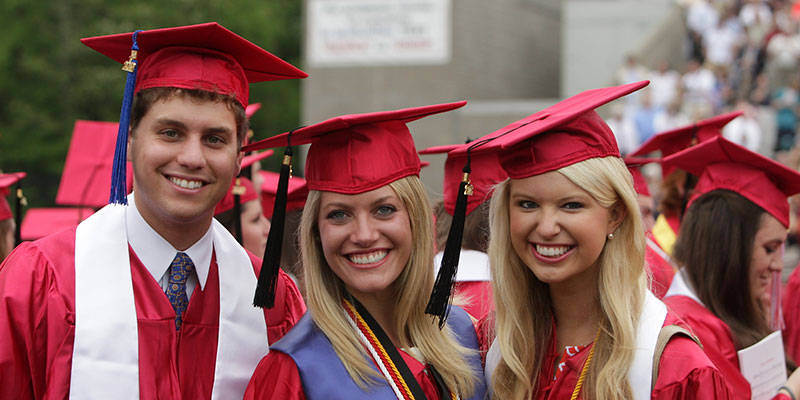 Three students in caps and gowns smile at commencement
