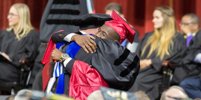An emotional hug between african american professor and student as the student receives his diploma on stage