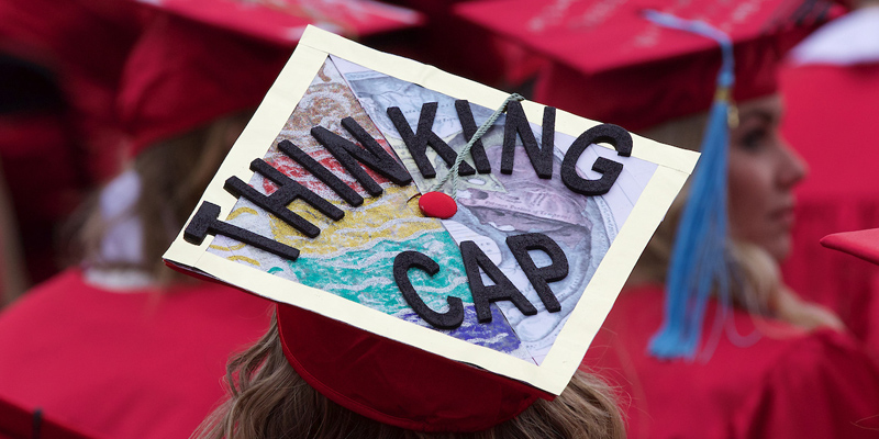 Many student choose to decorate their caps for all to see, this one says Thinking Cap with an illustration of the left and right brain hemispheres