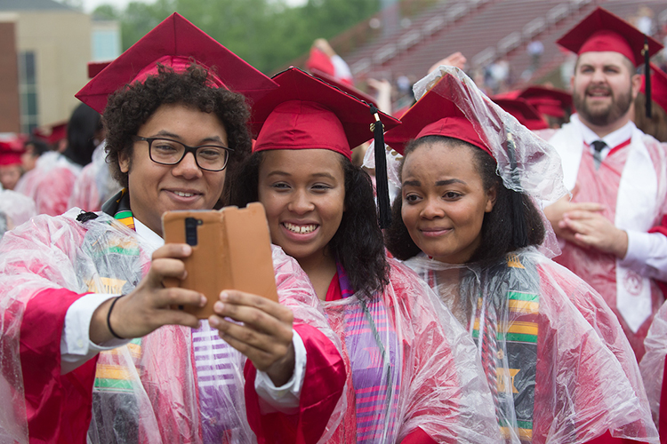 Three graduating students in rain ponchos take a selfie