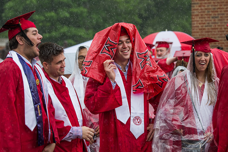 A graduating student covers his head with a rain poncho and smiles in the rain