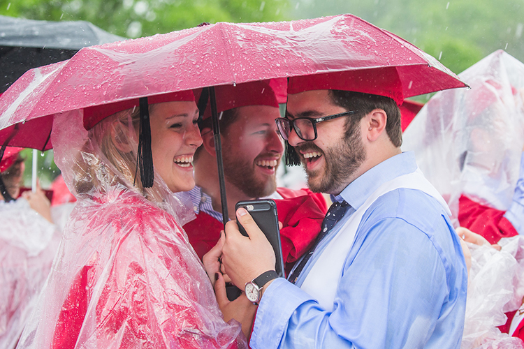 Three smiling students huddle under an umbrella