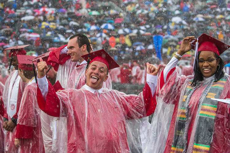A student gives the hang loose sign with his hands as he stands in the rain at commencement