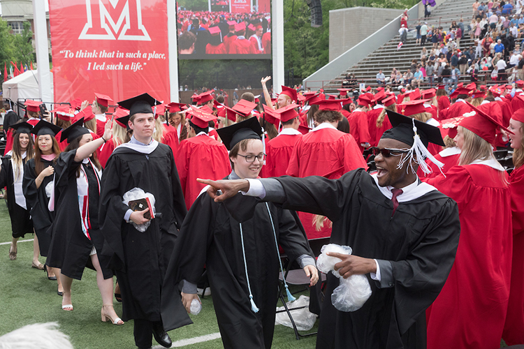 Graduate students walk down the center row at the end of the ceremony
