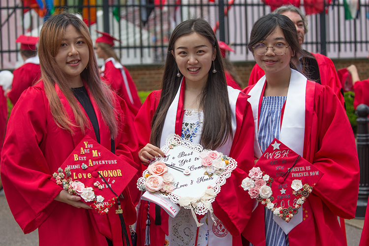 Three students smile and hold decorated graduation caps