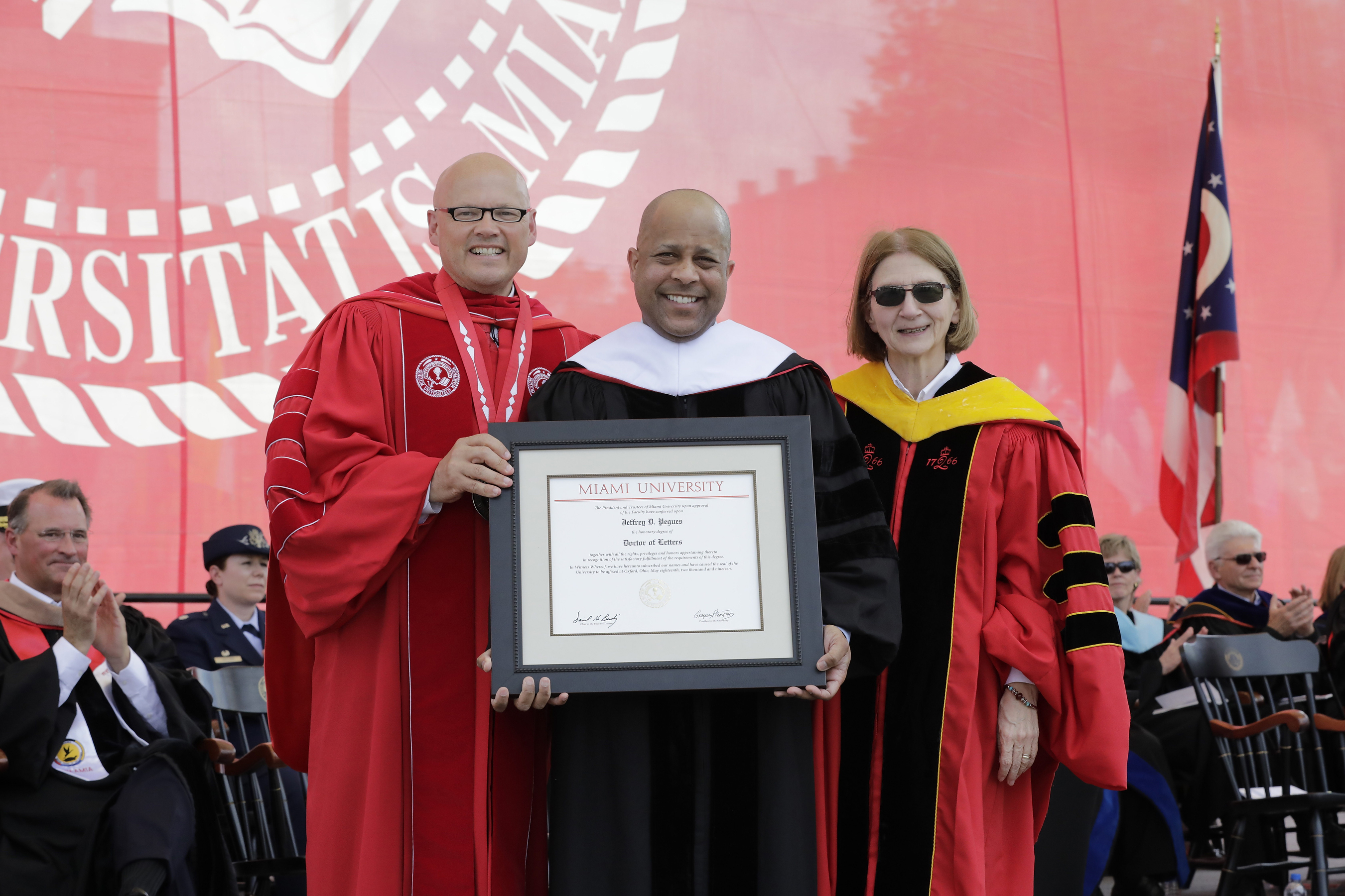 President Greg, Jeff Pegues and Phyllis Callahan are standing on stage while Jeff holds a certificate in his hands