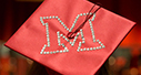 Red graduation cap with the Miami beveled M spelled with sparkly rhinestones