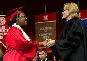 A student shakes hands with the dean as she receives her diploma