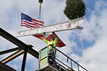 Construction worker putting final steel beam into place