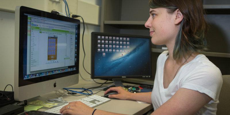 Rachel Kaczka sitting at desk with computer monitors