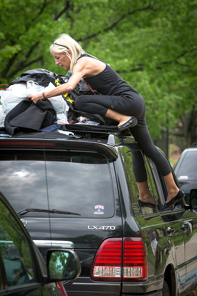 A parent is climbing on top of her car to attach things to its roof