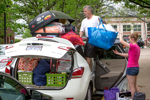 A parent and his daughter packing a very full car