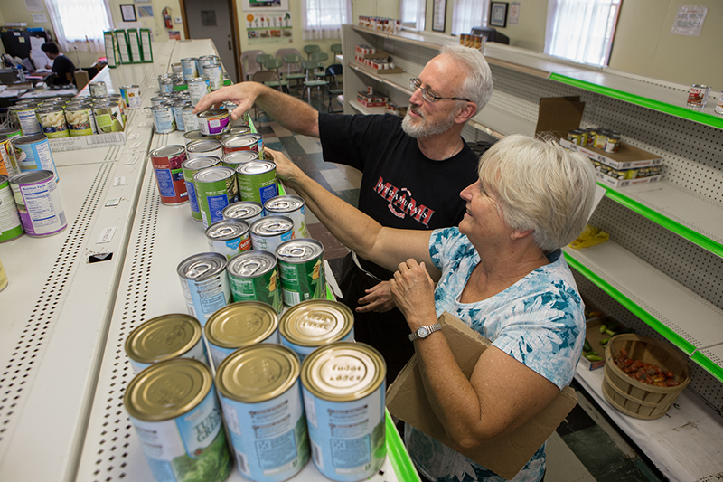 Pantry director Bob Ratterman and a community volunteer stock the shelves before customers arrive.