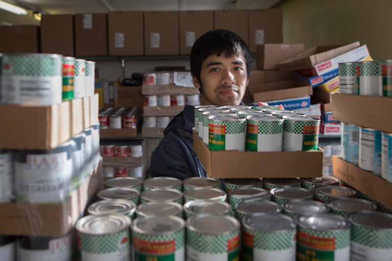 Peter Engelhard helps stock the pantry's shelves with canned goods.