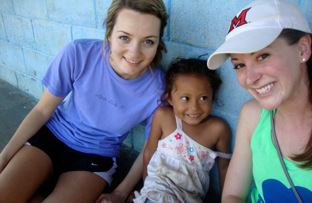 Amy Hutchison and Cara Demyan pose with a child