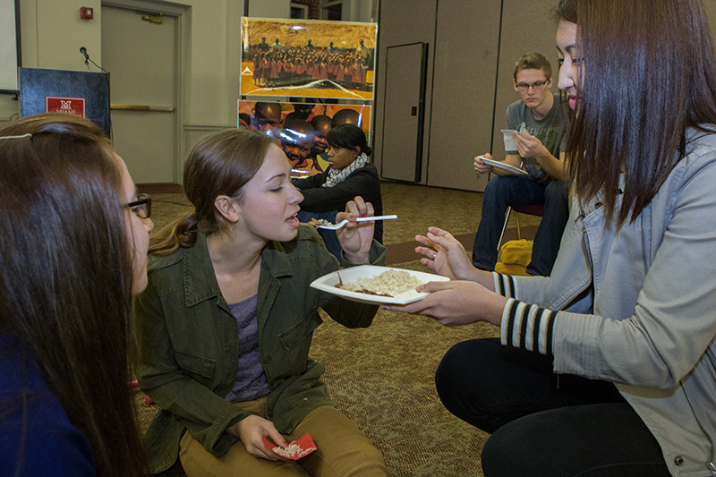 Participants in the Hunger Banquet, sponsored by Oxfam to teach about social issues, share their meals with one another.