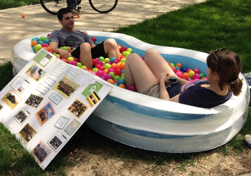 two students sitting in an inflatable pool with plastic balls