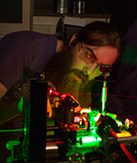 A physics student doing research using a laser machine