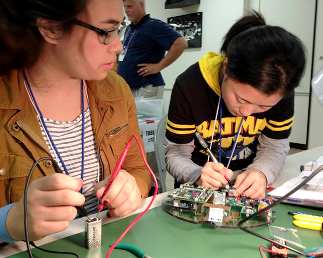 RockOn participants, Emma Kunimoto and Wei Lu, working on the payload