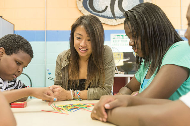At Chicago Youth Centers, Lisa Chiu plays a game of pick-up-sticks with the children.