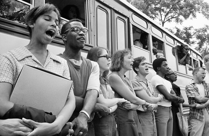Civil rights activists holding hands and singing next to a bus
