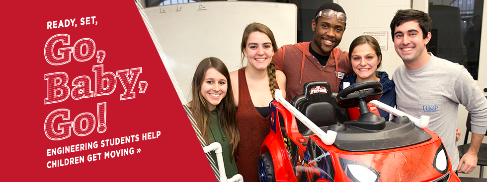 Ready, set, go, baby, go! Engineering students help children get moving » Photo of a group of 5 students posing with a battery-powered spiderman-themed kid-sized car modified to help children with mobility disabilities get around