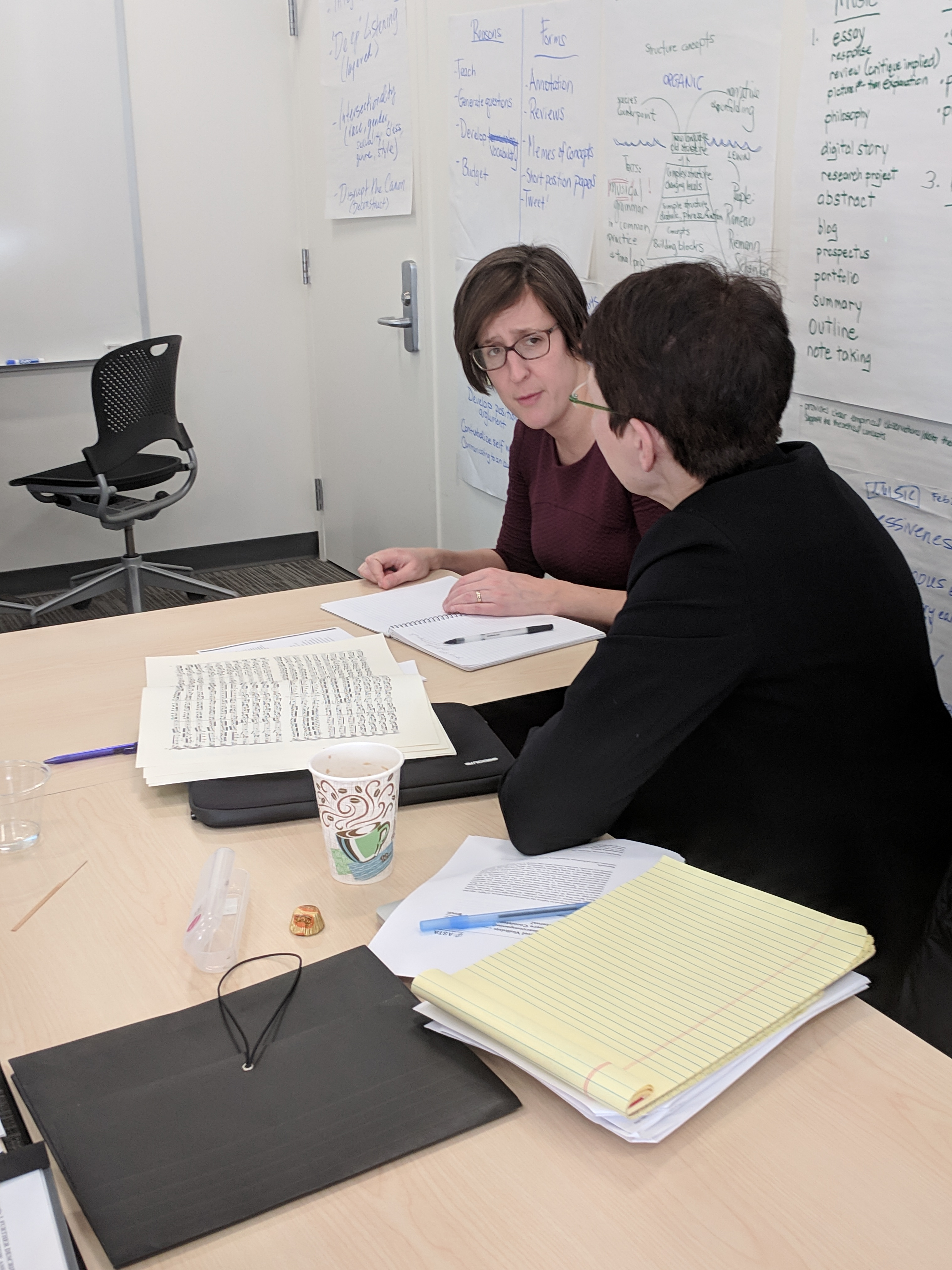 Brenda Mitchell (right) talks with Associate Professor of Art History Pepper Stetler (left) about a musical score during an HCWE Faculty Writing Fellows activity.