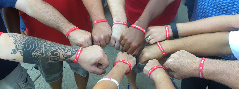 Miamians forming a huddle, extending their forearms to show their Love and Honor bracelets