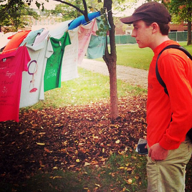 student looking at t-shirts hanging on clothesline