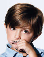 A boy using his finger as a mustache