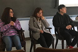 Three Chinese students sat in front of the room in a panel to answer questions.