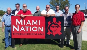 IT Services staff and Chief pose in front of Miami Nation sign
